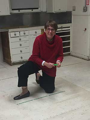 A woman measuring the San Jose Woman's Club's new floor