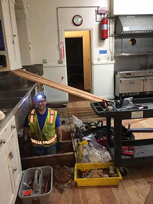 A worker removing the old floor of the San Jose Woman's Club kitchen