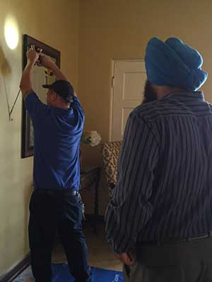 Men installing a security system at the San Jose Woman's Club